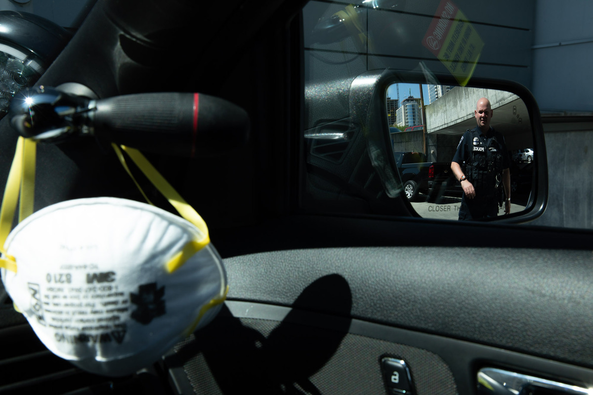 A Seattle Police officer seen in a sideview mirror