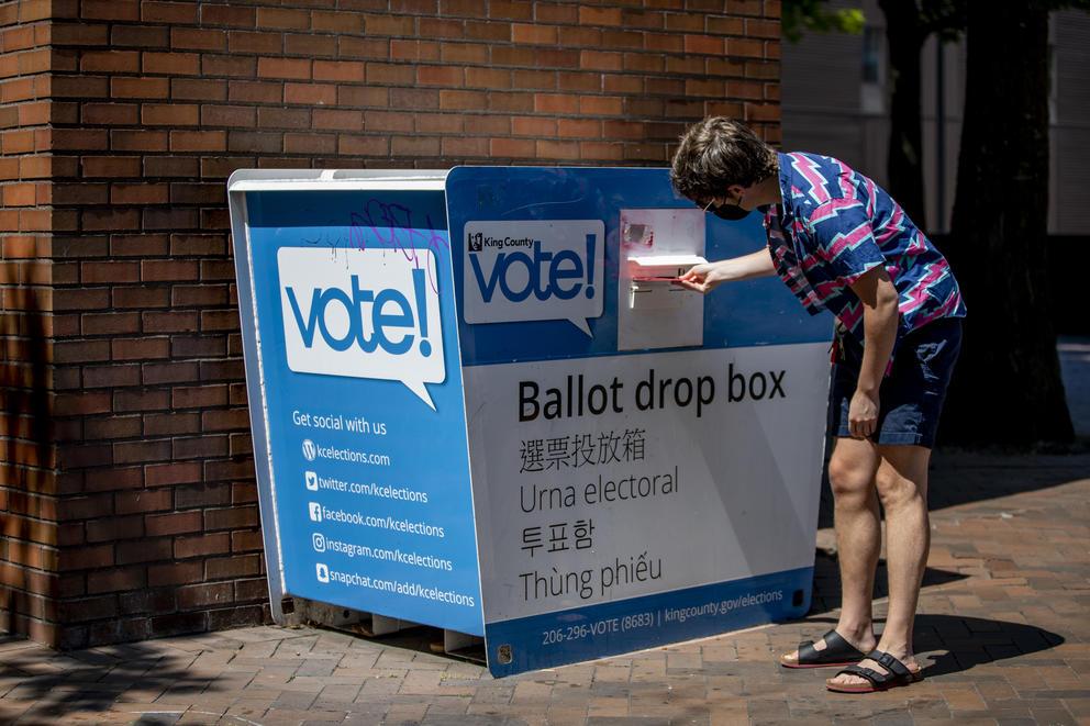 A person submits a ballot into a ballot drop box
