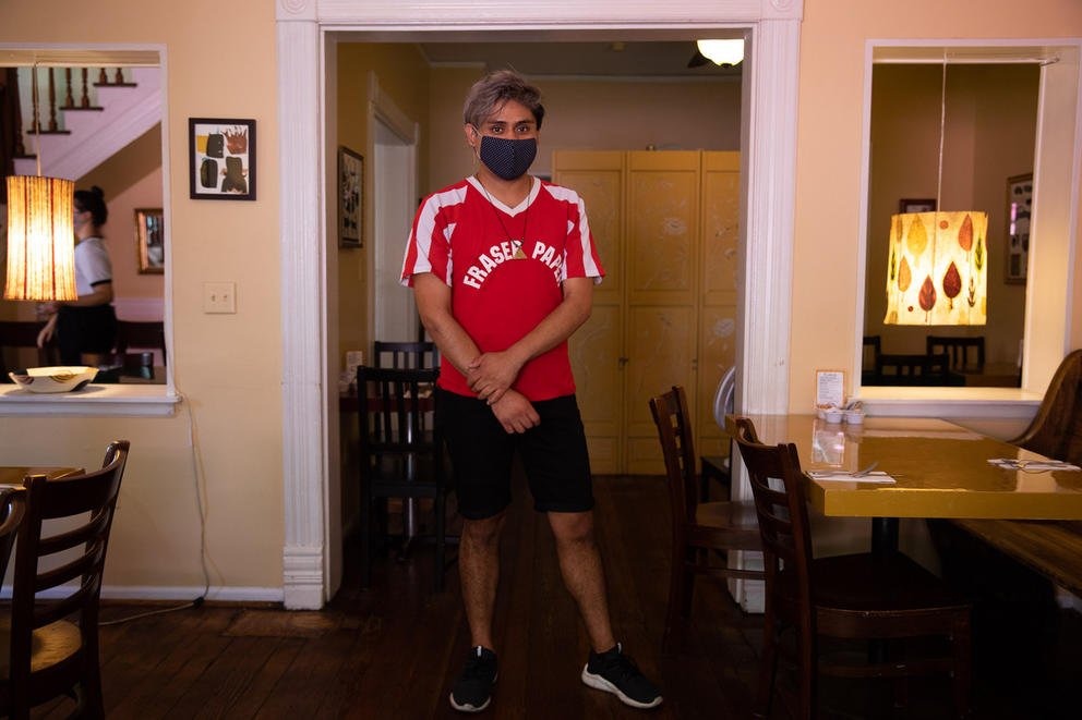A restaurant worker wearing a mask stands in his home.