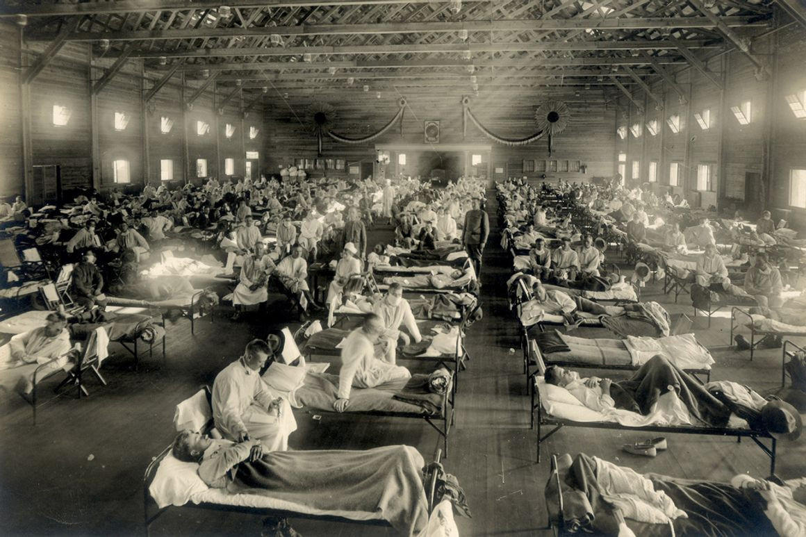 Health care workers tending to rows of patients in beds