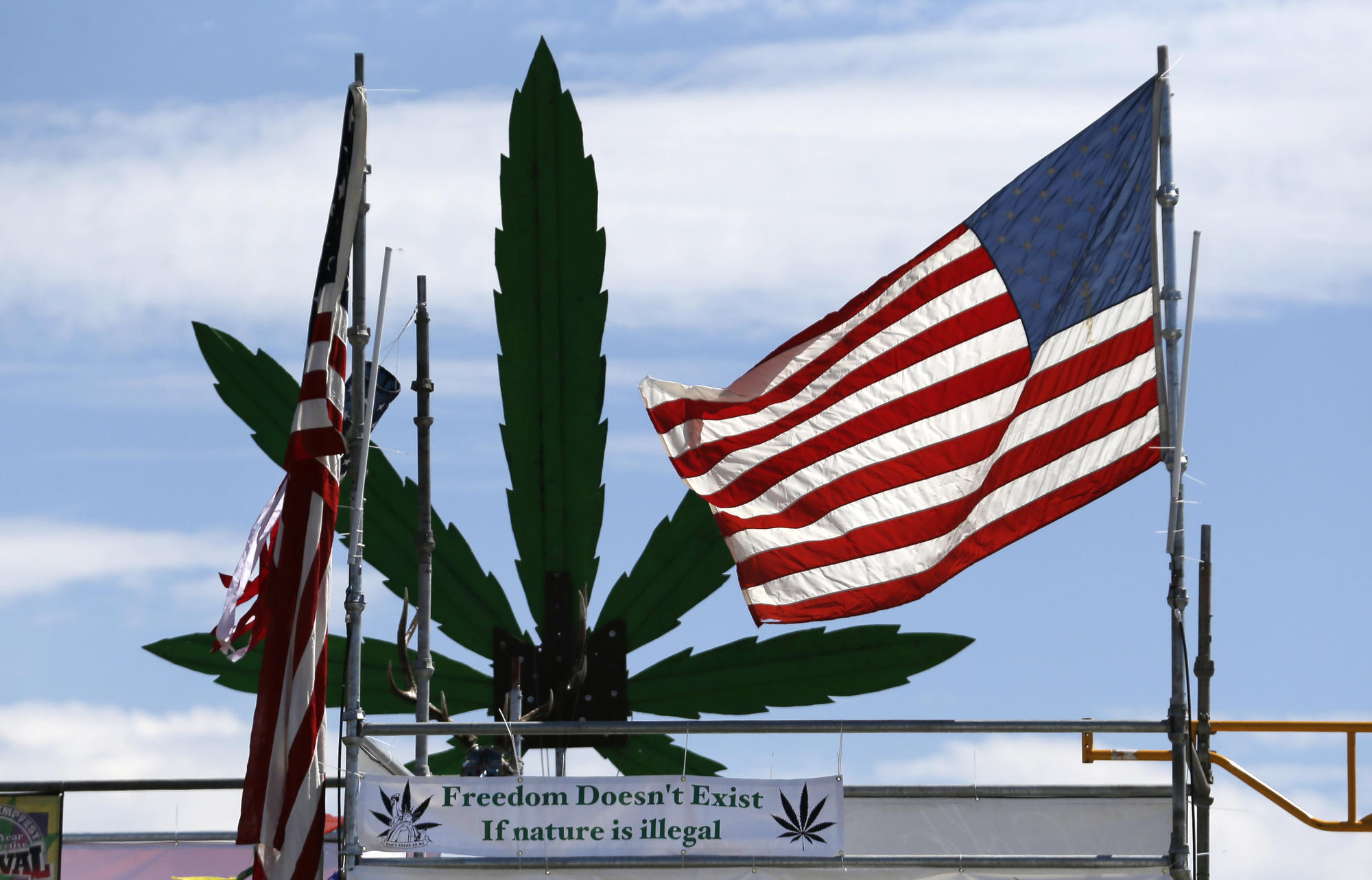 A U.S. flag flies in front of a hemp leaf at Hempfest