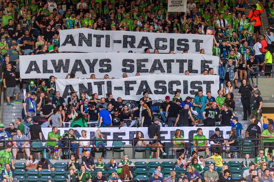 "Sounders fans in the stands hold a banner reading ""Anti-racist, always Seattle, anti-fascist"""
