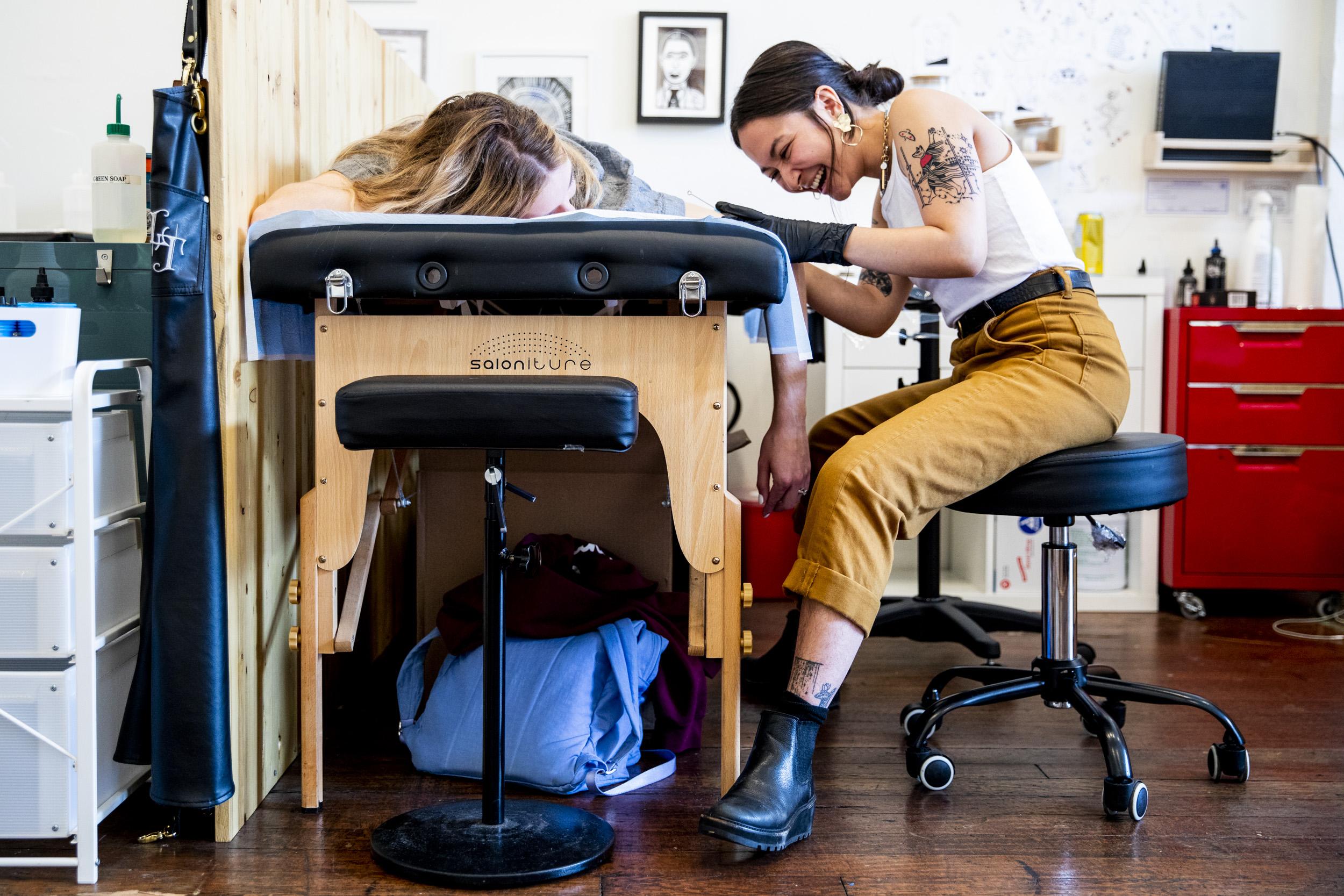 Tattoo artist Avery Osajima works on a client using the stick-and-poke method