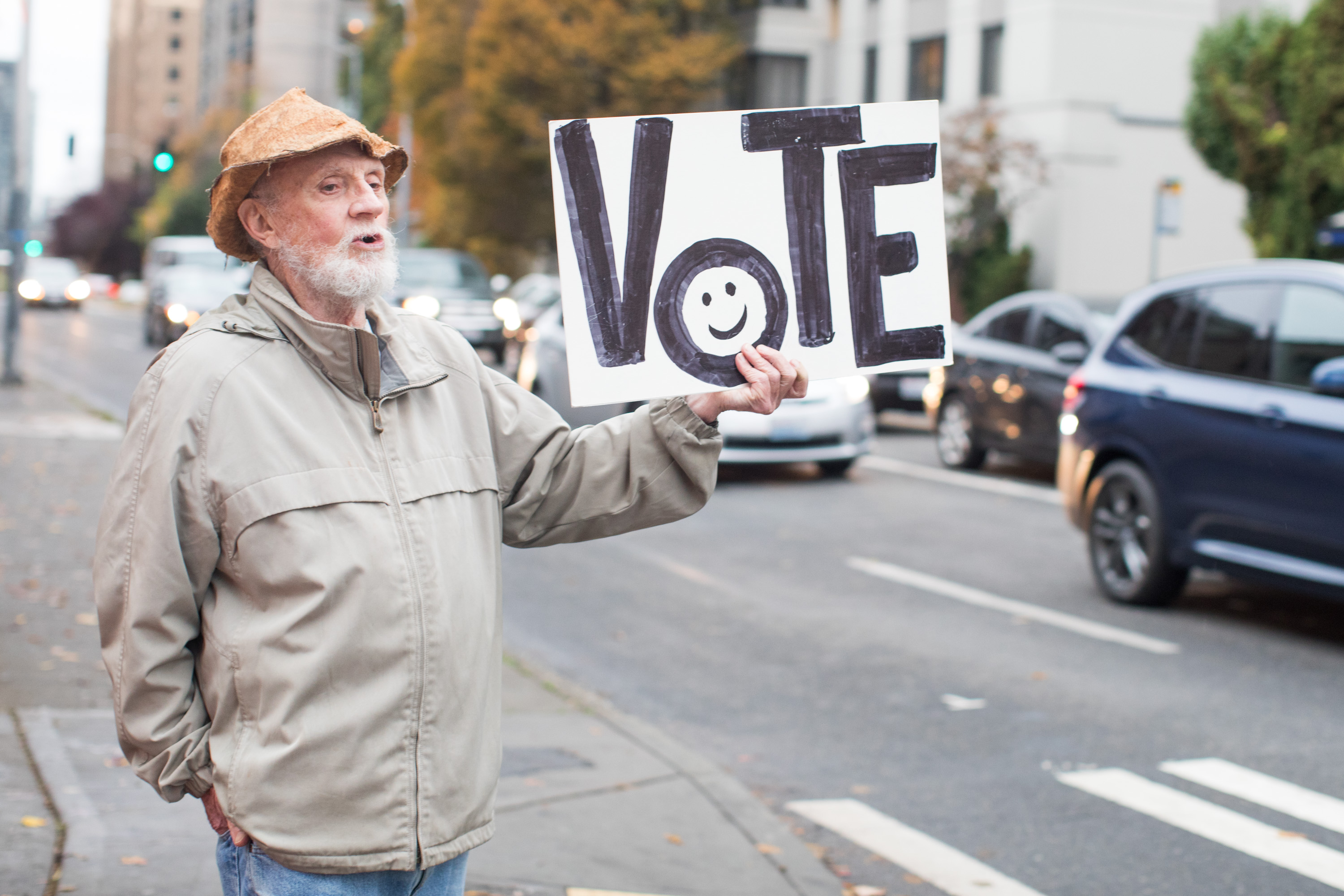 """A man holds a sign that reads """"VOTE"""" while standing on a sidewalk"""